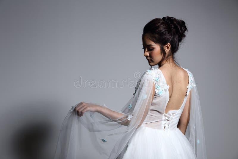 Älskvärd asiatisk härlig kvinnabrud i vit klänning w för bröllopkappa arkivbilder