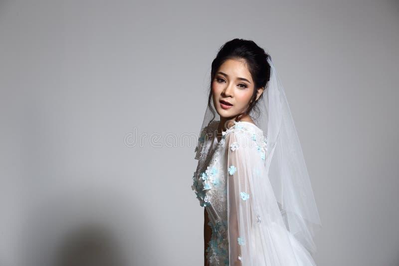 Älskvärd asiatisk härlig kvinnabrud i vit klänning w för bröllopkappa arkivfoto