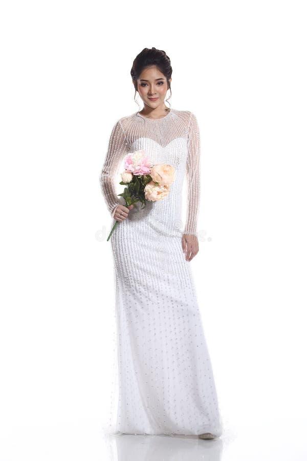 Älskvärd asiatisk härlig kvinnabrud i vit klänning w för bröllopkappa arkivfoton