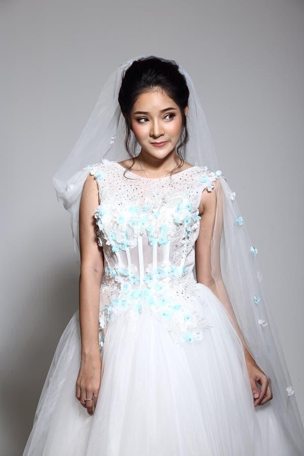 Älskvärd asiatisk härlig kvinnabrud i vit klänning w för bröllopkappa royaltyfri foto