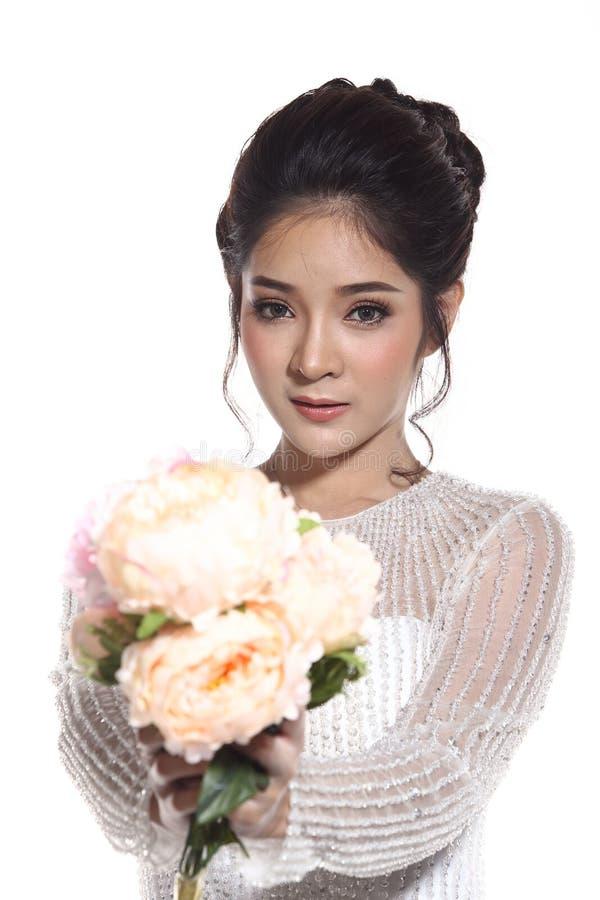 Älskvärd asiatisk härlig kvinnabrud i vit klänning w för bröllopkappa royaltyfri fotografi