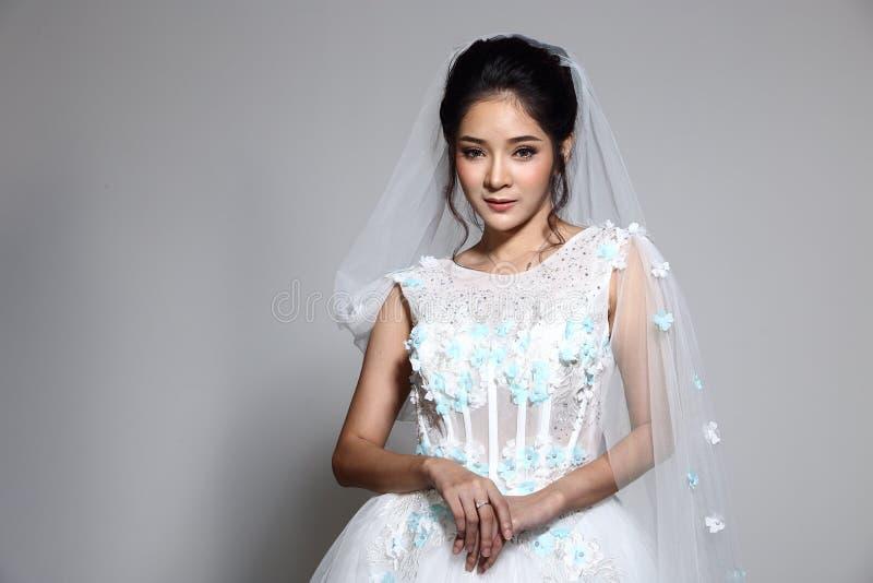 Älskvärd asiatisk härlig kvinnabrud i vit klänning w för bröllopkappa royaltyfria bilder