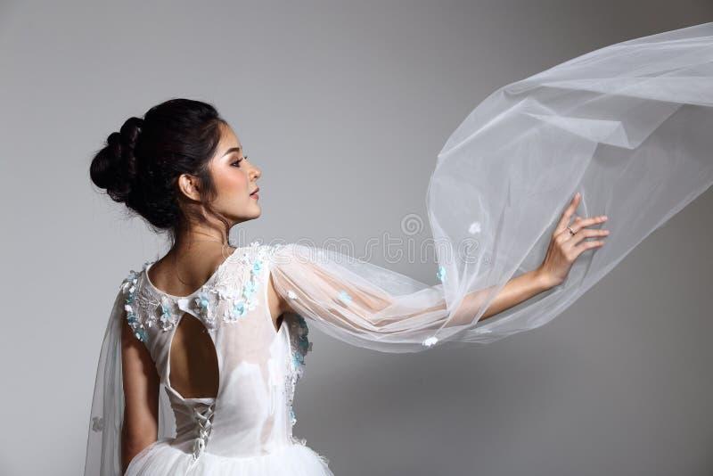 Älskvärd asiatisk härlig kvinnabrud i vit klänning w för bröllopkappa fotografering för bildbyråer