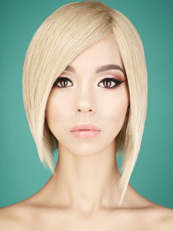 Älskvärd asiatisk kvinna med blont kort hår royaltyfri foto