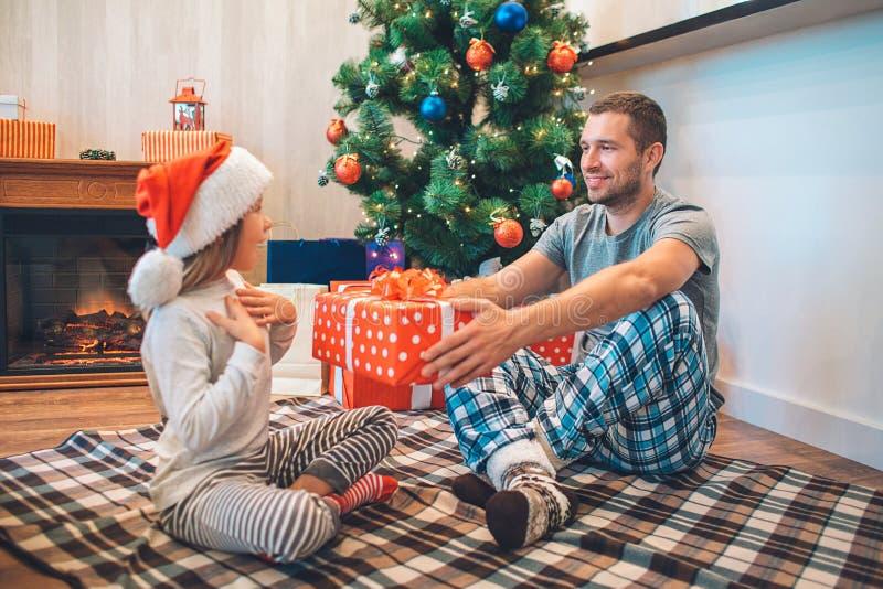 Älskvärd bild av fadern som ger gåvan till hans dotter Hon förbluffas Flickapunkter på henne och blickar på fadern Han är fotografering för bildbyråer