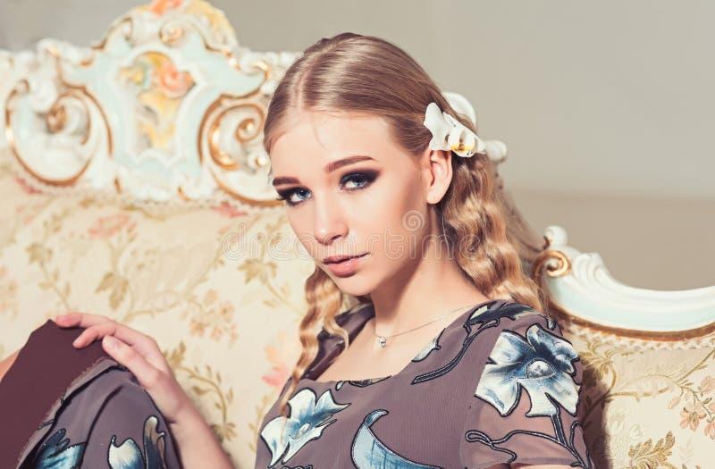 Älskvärd blond flicka med lockigt hår som sitter på tappningsoffan Closeupstående av den unga damen i blommig klänning royaltyfria bilder