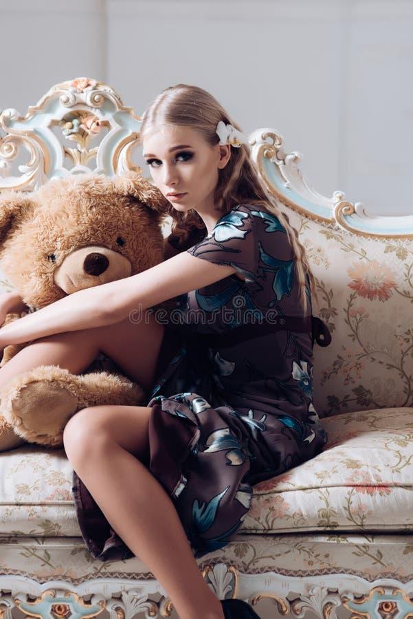 Älskvärd blond flicka som kramar den enorma nallebjörnen, medan sitta på den retro soffan Slank kvinna i blommig grå klänning i h royaltyfri bild