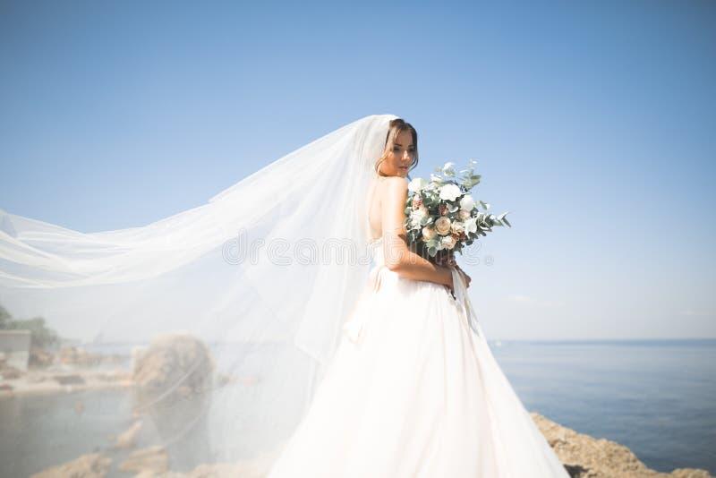 Älskvärd brud i den vita bröllopsklänningen som poserar nära havet med härlig bakgrund royaltyfri fotografi