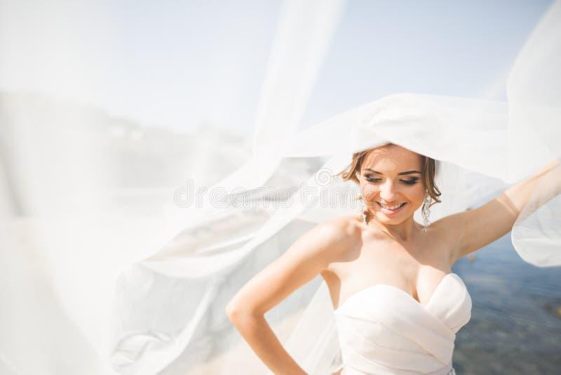 Älskvärd brud i den vita bröllopsklänningen som poserar nära havet med härlig bakgrund royaltyfri bild