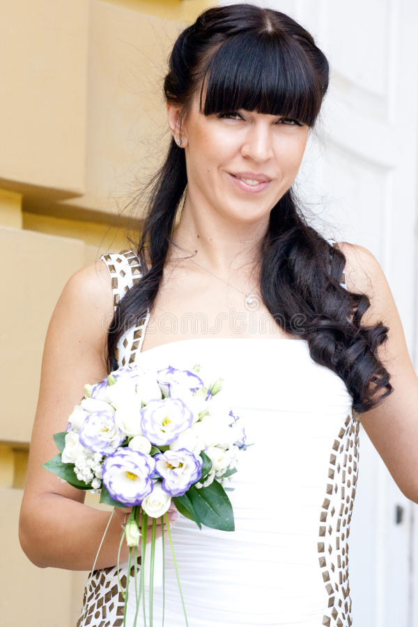 Älskvärd brud med buketten royaltyfri foto