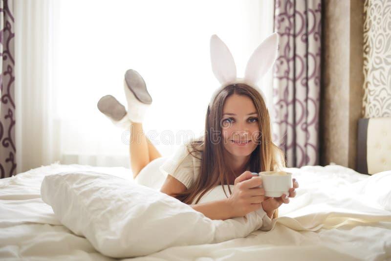 Älskvärd brunettflicka med kaninöron på hennes huvud och ligga med kaffe på en säng i hennes sovrum royaltyfria foton