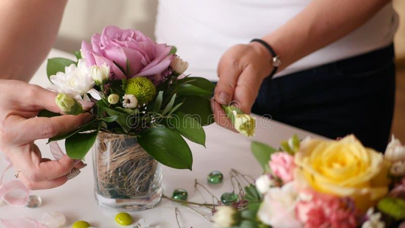 Älskvärd bukett av rosa färgrosen i en liten vas i händerna av en härlig ung flicka HD fotografering för bildbyråer