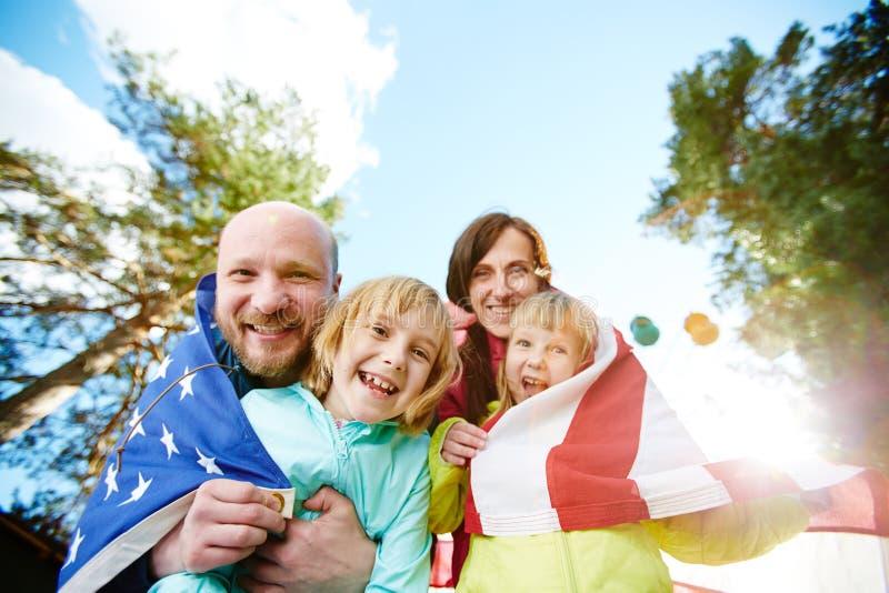 Älskvärd familj med amerikanska flaggan fotografering för bildbyråer
