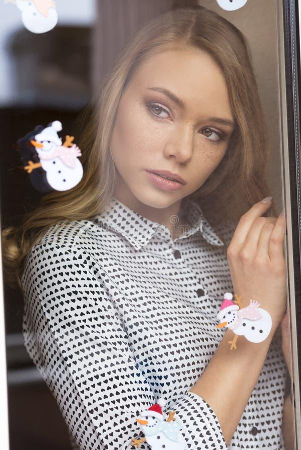 Älskvärd flicka bak fönster royaltyfri fotografi
