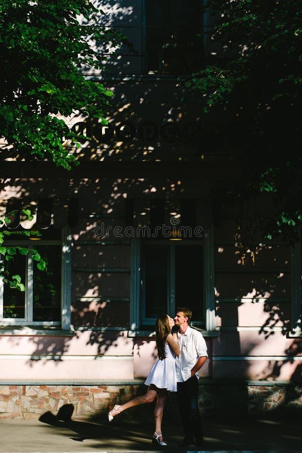 Älskvärd flicka i vitt kyssa hennes man i en kind fotografering för bildbyråer