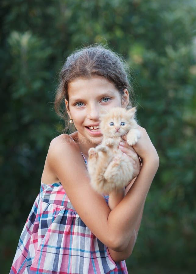 Älskvärd flicka med den gulliga kattungen royaltyfri foto