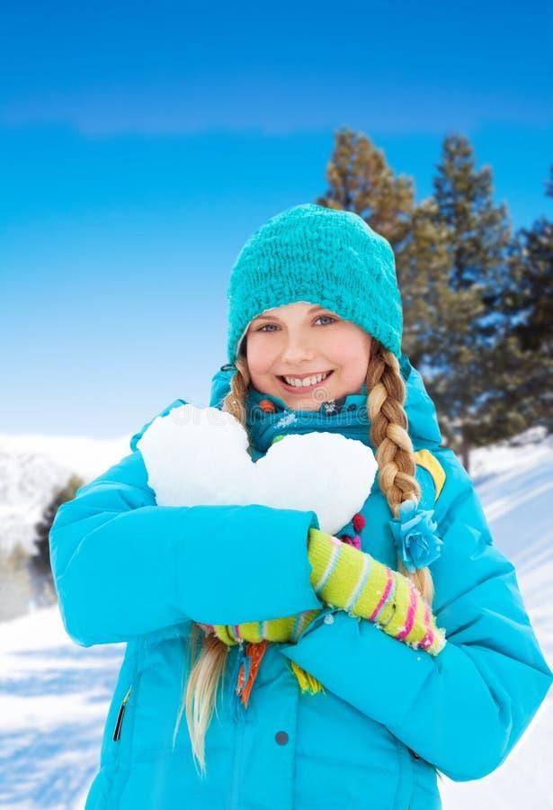 Älskvärd flicka med hjärta som göras av snö royaltyfria bilder