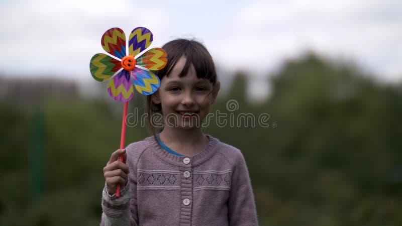 Älskvärd flicka med väderkvarnleksaken på naturen som ler och ser kameran royaltyfria bilder