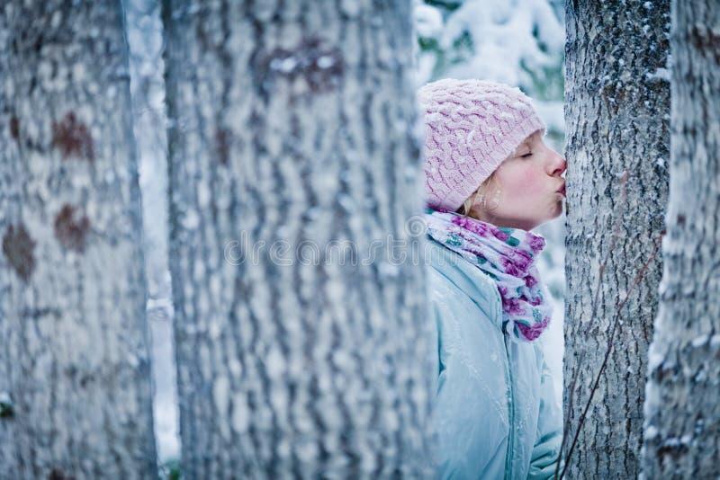 Älskvärd flicka som kysser ett träd i skog fotografering för bildbyråer