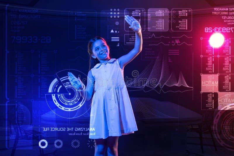Älskvärd flicka som sätter två händer på skärmen och le royaltyfria bilder