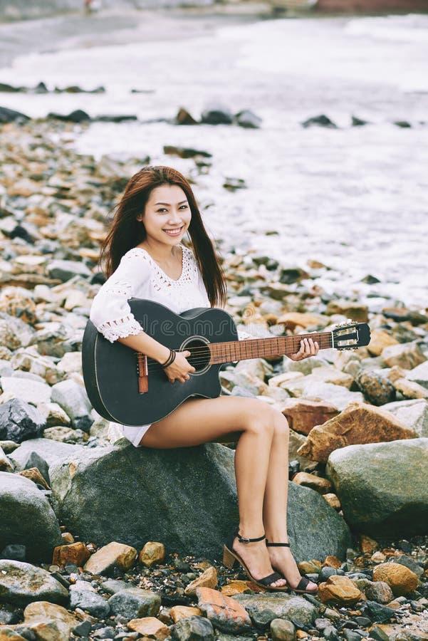 Älskvärd flicka som spelar gitarren fotografering för bildbyråer