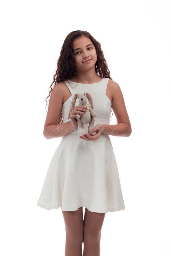 Älskvärd flickabrunett med långt hår i en vit klänning med en vit kanin för mjuk leksak i händer på en vit bakgrund arkivfoton