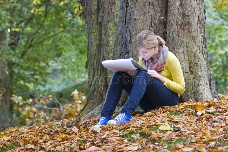 Älskvärd flickateckning i parken royaltyfri fotografi