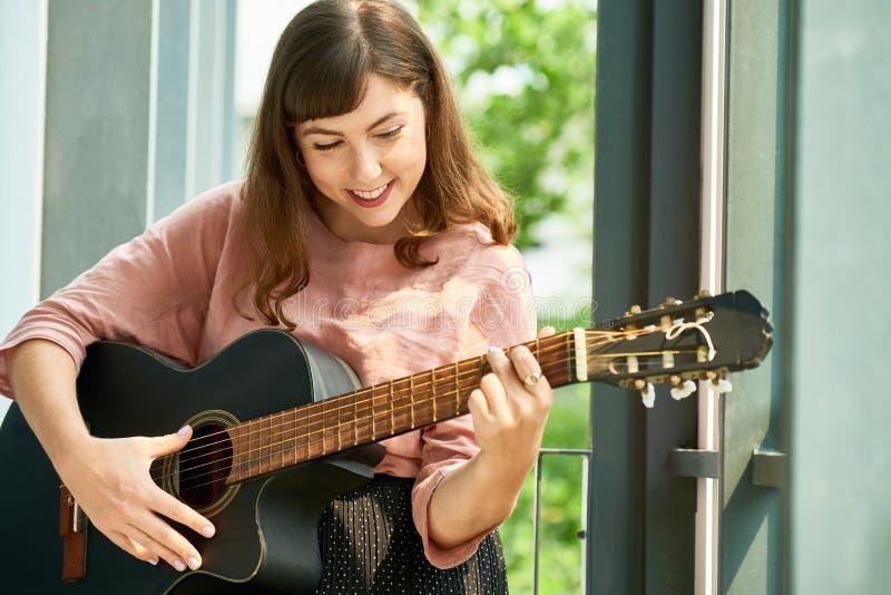 Älskvärd gladlynt kvinna med gitarren royaltyfri fotografi