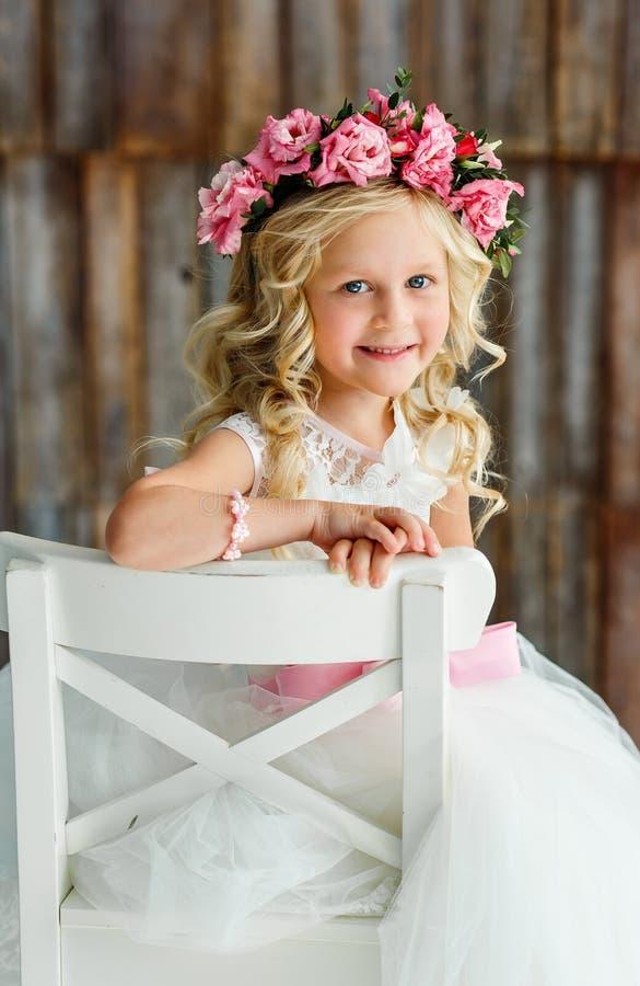 Älskvärd gullig liten flicka - blondin i en krans av levande rosor i en vit härlig klänning i en ljus studio royaltyfri foto