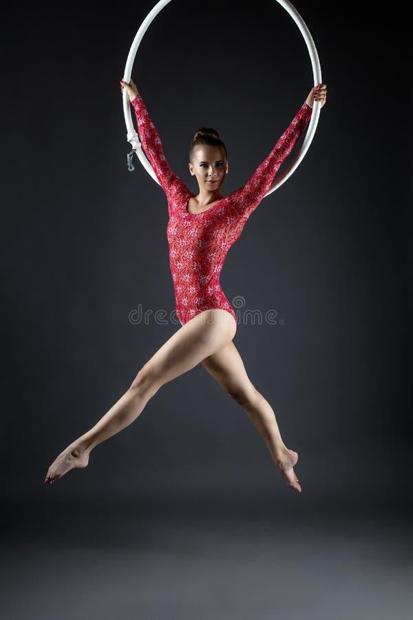 Älskvärd gymnast som poserar, medan utför med beslaget royaltyfri fotografi