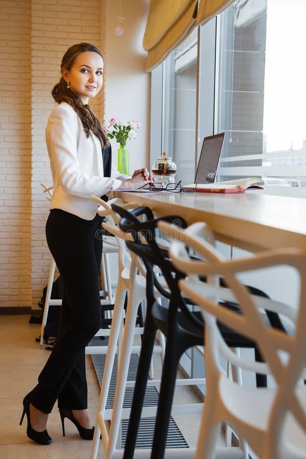 Älskvärd kvinna i affärsdräkten som står nära tabellen med bärbara datorn arkivbild
