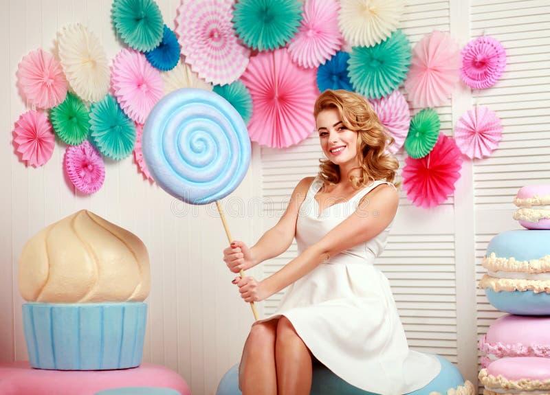 Älskvärd kvinna med enormt marshmallow- och kakasötsakbegrepp arkivbild