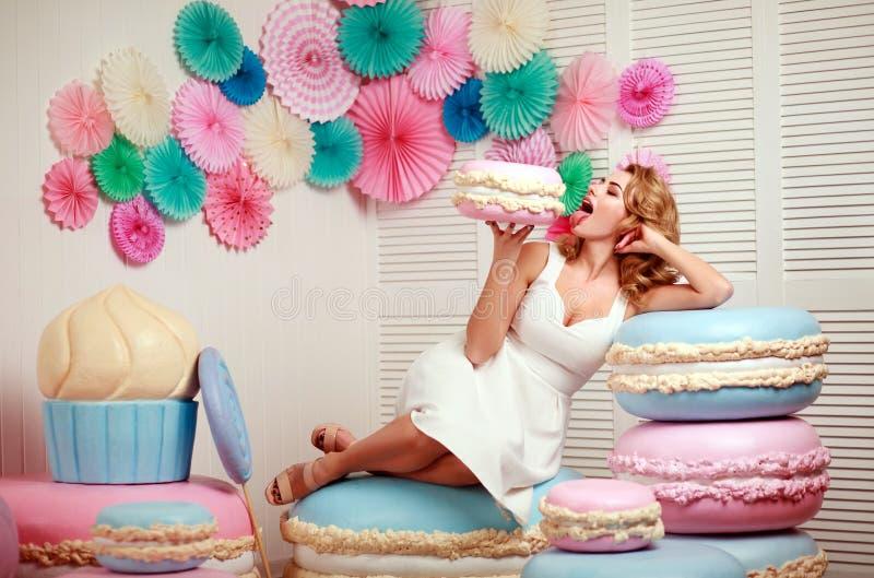 Älskvärd kvinna med enormt marshmallow- och kakasötsakbegrepp royaltyfri foto