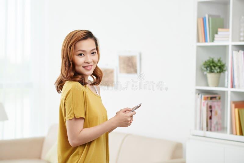 Älskvärd kvinna med smartphonen royaltyfri foto