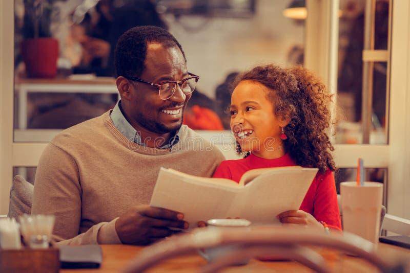 Älskvärd läsebok för fader- och dotterkänsla tillsammans royaltyfri foto