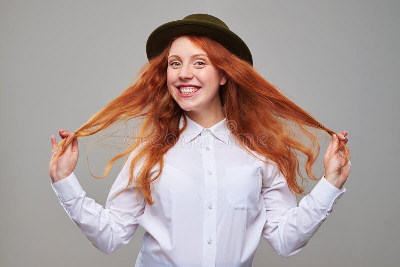Älskvärd lång röd hårflicka i svart hatt arkivfoton