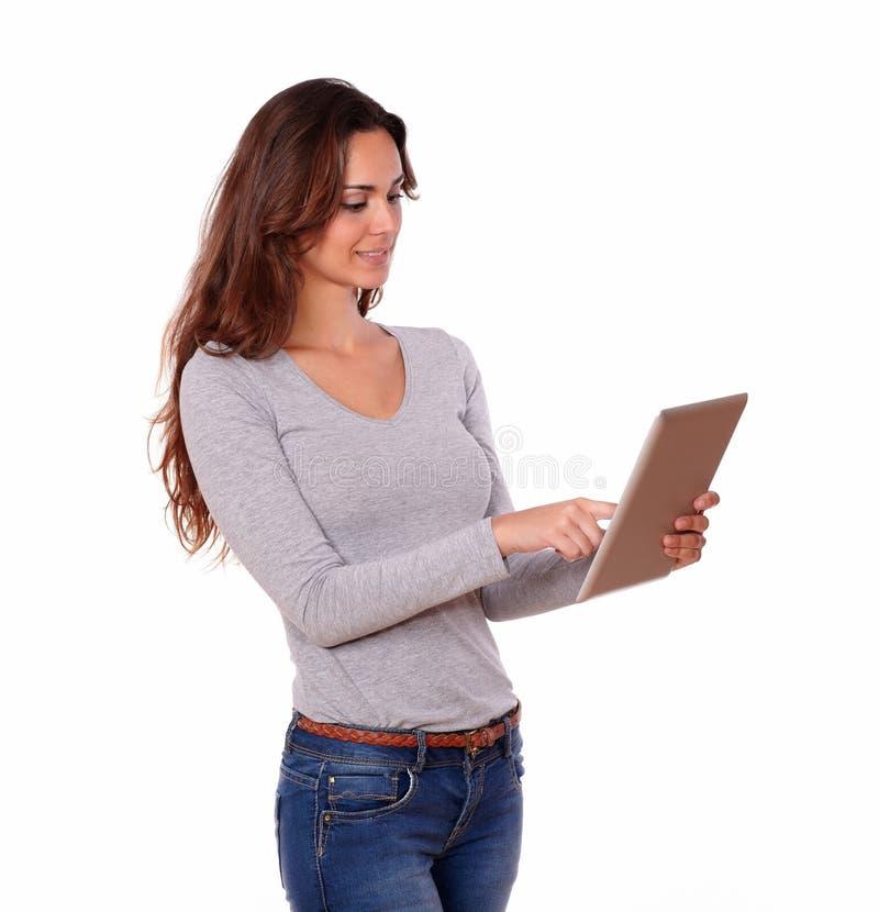 Älskvärd latinamerikansk kvinna som arbetar på minnestavlaPC royaltyfri bild