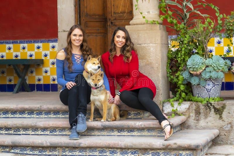 Älskvärd latinamerikansk modell Poses Outdoors With för brunett två deras husdjur på en mexicansk ranch royaltyfria bilder