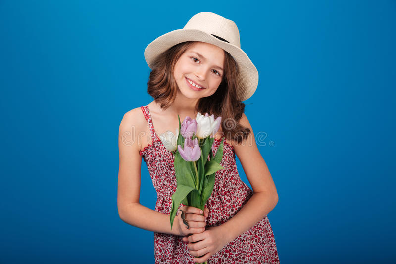 Älskvärd le liten flicka i hatt med buketten av blommor royaltyfri bild
