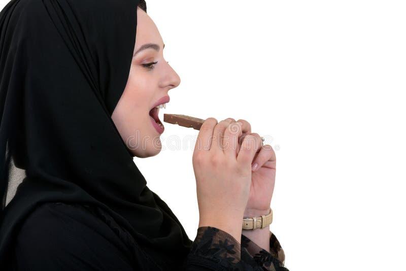 Älskvärd le muslimkvinna med hijab som äter choklad som isoleras på vit bakgrund royaltyfri bild