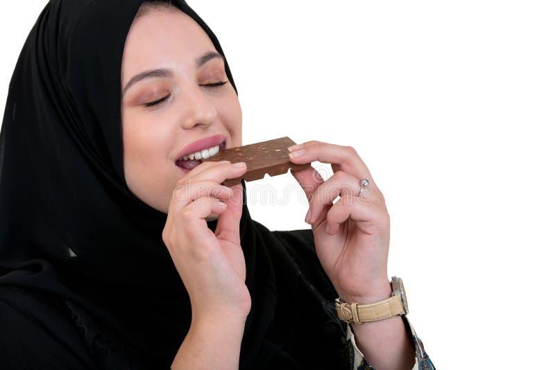 Älskvärd le muslimkvinna med hijab som äter choklad som isoleras på vit bakgrund arkivfoto
