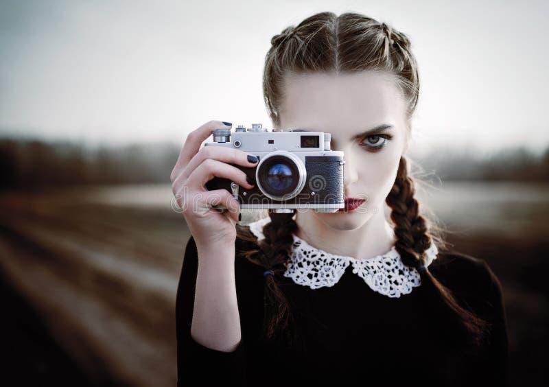 Älskvärd ledsen ung flicka som fotograferar på tappningfilmkamera Utomhus- stående för Closeup royaltyfri fotografi