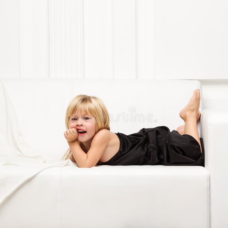 Älskvärd liten flicka i klänningen på soffan arkivfoton