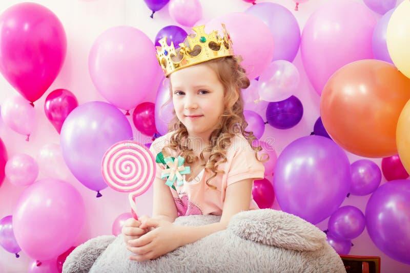 Älskvärd lockig flicka som poserar i krona med klubban arkivfoton