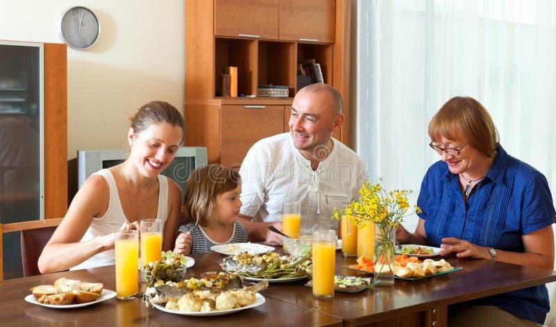 Älskvärd lycklig multigeneration familj som har den sunda matställen royaltyfri fotografi