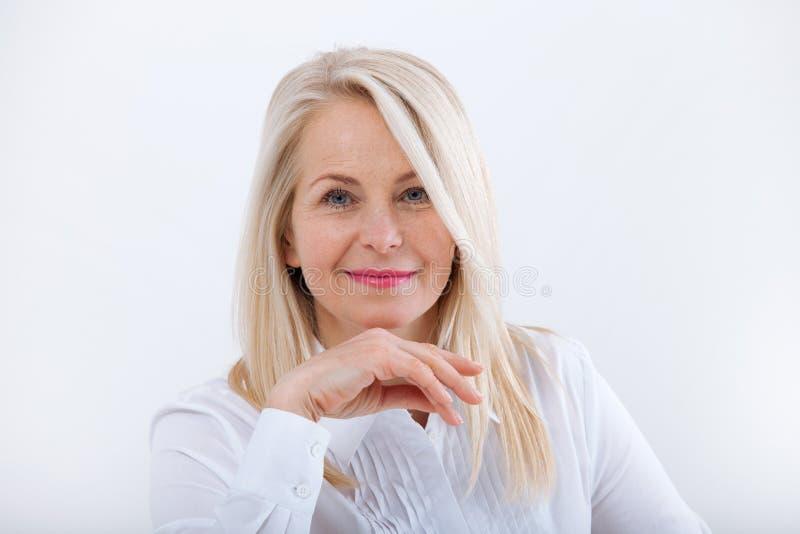 Älskvärd medelålders blond kvinna med ett stråla leendesammanträde på kontoret som ser kameran arkivbild