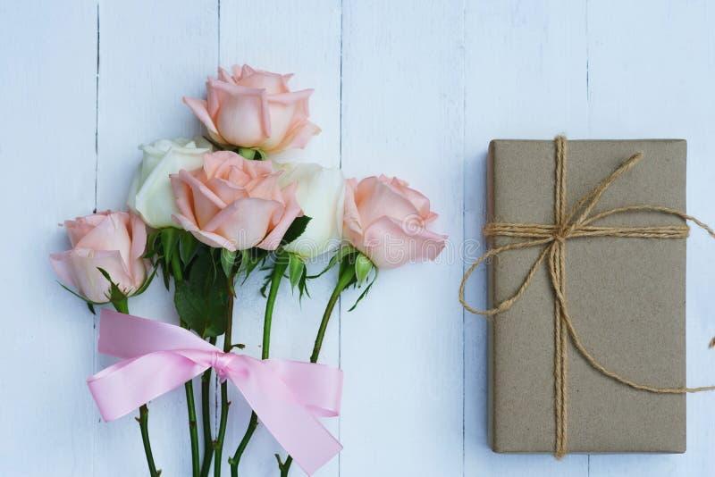 Älskvärd mjuk orange rosa färgros som binds av det rosa bandet och den bruna gåvaasken på vit trätabellbakgrund, söt valentingåva arkivbild