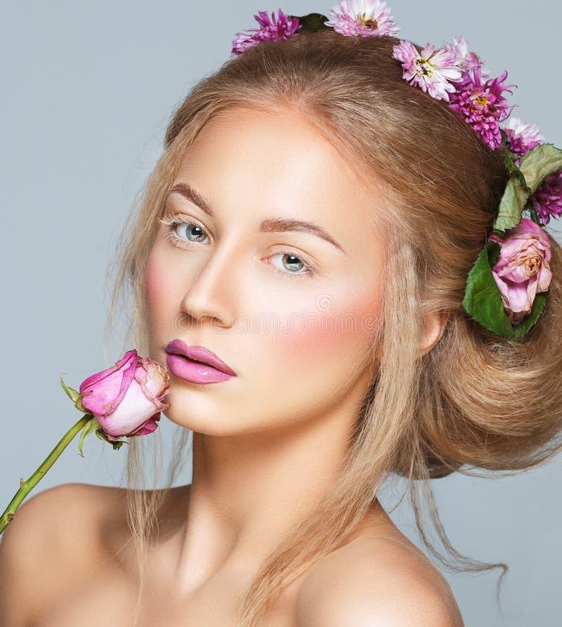 Älskvärd modell med lockigt hår för skinande volym med blommor, vinter w royaltyfri bild