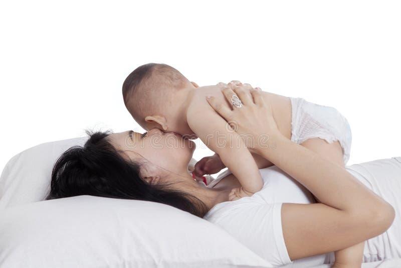 Älskvärd moder som kysser hennes dotter på säng arkivfoto