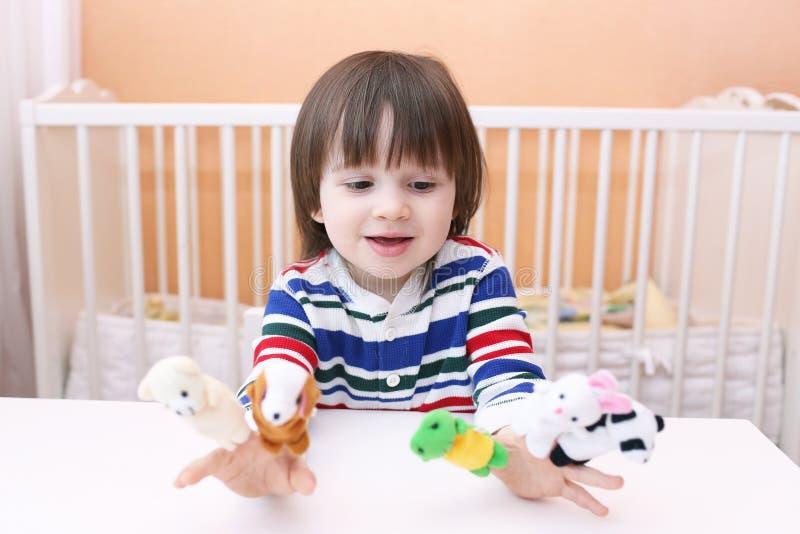 Älskvärd pys (2 5 år) lekar med fingerdockor hemma royaltyfri foto